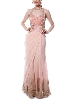 Perfect for the modern woman with a flair for tradition, this light pink saree gown from Mandira Wirk offers pretty detailing and a flattering silhouette. This draped saree features lovely draped detailing and stylish tonal sleeveless bodice adorned with resham embroidery and sheer detailing.