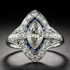 A sparkling European-cut marquise diamond, weighing three-quarters-of-a-carat, glistens and gleams from atop an artfully handcrafted platinum mounting designed and rendered to accentuate the sleekly fashioned shape of the stone. The marquise is outlined by slender royal-blue calibre-cut sapphires interrupted, east and west, by a pair of round diamonds which lead, in turn, to a hand-engraved design on the shoulders. North and south glitters with diamond-set chevrons.