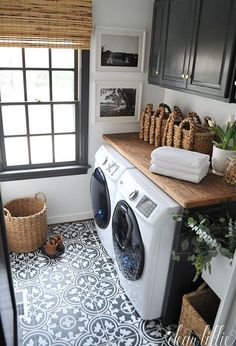 Love this laundry design with cement tiles, wood accents, and dark cabinets