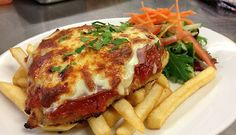 Chicken Parmigiana - Chicken parmigiana is a popular Australian and Italian-American dish consisting of a crumbed (breaded) chicken breast topped with pasta (tomato) sauce and mozzarella, parmesan or provolone cheese. A slice of ham or bacon is sometimes added - http://aussietaste.recipes/chicken/chicken-parmigiana/ - #recipe