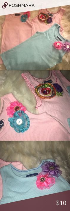 Girls Tank Tops (3) 3 (2 Pink, 1 Blue) girls tank tops with custom details. 100% Cotton ribbed tank tops with had sewn flowers details. Made in Dominican Republic by my daughter's grand mother using regular Cotton tank tops (old navy) and handmade fabric flowers.   Shirts are of course worn but in excellent condition. Flower detail is on shoulder of each tank top. Price is for all 3.  My daughter absolutely loved these tops and hopefully they can find a new living home! Sized S 6/6x Old Navy…