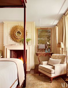 A sunburst mirror is displayed above the fireplace in a guest room of an upstate New York home renovated by architect John I. Meyer Jr. and design firm McAlpine Booth & Ferrier Interiors.