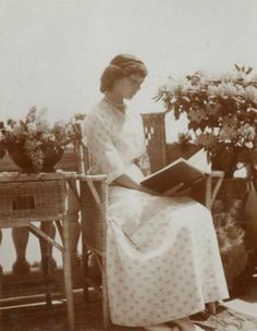 Tatiana, the second sister, posed with a book and surrounded by flowers.