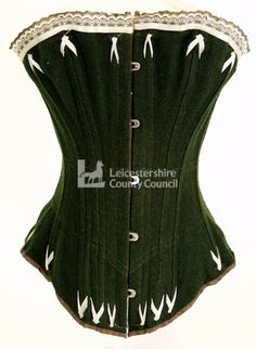 Woman's corset of 1900, in heavy green flannelette, lined with twill. Features a straight front, steel boning, and machine flossing.   A busk front corset produced in 1900. It is made from a heavy green flannelette, which has been lined with brown twill.  The corset has a straight front style, which was typical of the late 19th century, and is supported with wide, flat steel boning.   Machine-stitched flossing in a pale green colour has been used around the top and bottom of the corset. The…