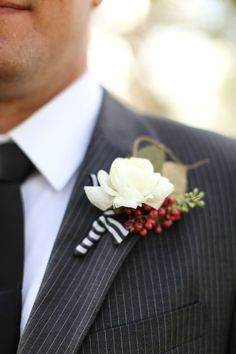 White Rose Boutonniere: Winter goes preppy with a striped ribbon and white rose. If you're planning a country club wedding, this simple classic will make all the men look dapper.   10 Winter Groom's Boutonnieres For Your Winter Wedding