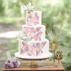"""""""3 tiered simple white cake decorated with lavender, pink, and dusty pink mosaic harmonized with 2 strategically placed flowers. Nothing shouts artsy art…"""""""