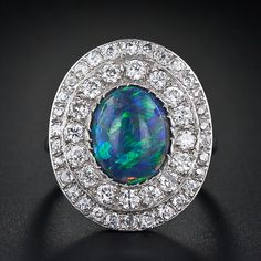Edwardian platinum ring highlighting a 2.25 carat oval black opal cabochon dancing with blue and green play of color and wrapped in a double border of bead set European cut diamonds (1.75 carats total weight, F-H color, VS-SI clarity).