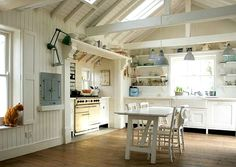 Love the high beamed ceilings, shelves flanking the farmhouse sink and neutral color scheme.