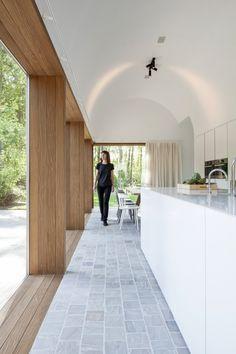 Architecte Sofie Ooms ontwierp voor haar zus Dorien een rustgevende thuis in het groen, waar ze zich altijd op vakantie kan voelen. Een zeer minimalistische inrichting met grote glaspartijen zodat de natuur bijna binnen in de woning zit.