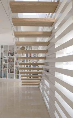 escalier suspendu en bois naturel clair et intérieur blanc