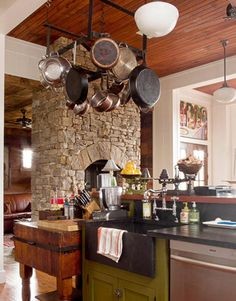 """The old butcher block and the iron pot rack were made by the same manufacturer and found at an antiques store. The farmhouse-style sink and the countertops are made of soapstone from Vermont Soapstone. """"Even honed granite would have looked too new for this kitchen,"""" says Kettles. Country Kitchen Bridge faucet by Rohl. Dishwasher by Bosch.   - HouseBeautiful.com"""