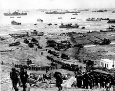 Allied forces bringing in troops and equipment at Omaha Beach after it was...