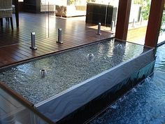 """Rippled Waters 5.....Two water features in one!   Rippled Waters design with a Sheer Descent. Water pumps from 3 spouts rippling over reservoir surface and flows a sheet of water into our clients inviting lap pool.  The curved etched lines on the stainless steel sheer descent panel really add the """"wow factor""""."""