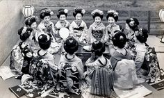 In a Circle 1930s. A group of Maiko Girls (Apprentice Geisha) seated in a circle. They all appear to be from different Okiya (Geisha Houses), judging by the Kamon (Crests) on their Obi. I really like the Obi of the girl second from the right, which has stylised Plovers (birds) on it.