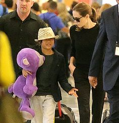 Angelina Jolie walks with Pax Pitt-Jolie, who's carrying a large purpe stuffed animal at JFK Airport in NYC on June 24, 2013.