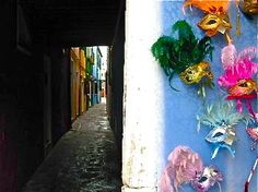 Colors: Venetian masks on display near an alleyway in Burano, Italy - Photograph taken by Bonechi Imports