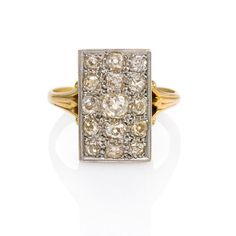 Mann's Jewelers An Edwardian ring comprised of a rectangular pavé diamond plaque with pierced gallery and scrolled shoulders. The ring is set with 15 old mine cut diamonds (atw. 1.40 ct.) in 18K gold and platinum.