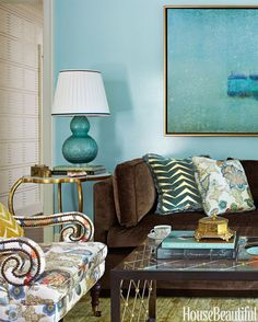 In the living room, Harper re-covered the clients' old sofa in a Duralee brown cotton velvet — a masculine foil for the blue walls. Lee Jofa's Arcadia on Jayson Home's Penelope chair. Lamp, Darnell & Company.