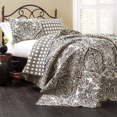 This quilt features a damask pattern with paisley along with a geometric pattern on the reverse, all in an intense contrasting light and dark scheme. Two lovely matching shams are included in the machine washable set.