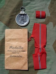Die Medaille Winterschlacht Im Osten 1941/42 (Ostmedaille) Eastern Front Medal; Awarded to all German military personnel who participated in the first winter of Operation Barbarossa (the invasion of the Soviet Union). In this photo, it appears with with Issue Packet and Ribbon Bar.