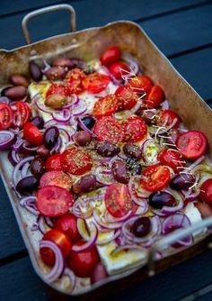 Detta är vansinnigt gott! Bakad fetaost med tomat, oliver, lök och oregano. Jag bakade min fetaost på grillen. Det blev ett fantastiskt gott tilltugg vid maten. Vi bröt en bit bröd och doppade det direkt i formen. Fetatosten var ljuvlig när den var varm. Man kan även baka osten i ugnen. Servera som en förrätt, ett gott tilltuggg vid maten eller som en varm sallad. 6 portioner 3 st block fetaost (150 g styck) 400 g coktailtomater 1 rödlök Ca 1,5 dl kalamataoliver 0,5 dl olivolja 1 msk torkad o...