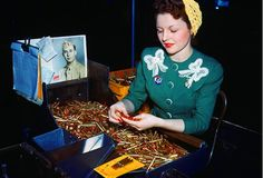 Woman Inspecting Bullets: Fee Perez inspects caliber rifle and machine gun bullets at Remington Arms Company's Bridgeport, Connecticut, plant alongside a photo of her husband, Melburn, who is serving overseas. 1940s Fashion, Vintage Fashion, Vintage Beauty, Vintage Style, Women's Fashion, Rosie The Riveter, Working Woman, Women In History, Vintage Sweaters