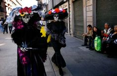 "Women dressed as traditional Mexican ""Catrinas"" walk through downtown for Day of the Dead celebrations in Mexico City, Sunday Oct. 30, 2011.  Mexicans celebrate Day of the Dead to honor deceased loved ones, a tradition that coincides with All Saints Day and All Souls Day on Nov. 1 and 2. Photo: AP / SA"