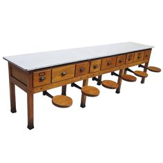 Early 20th Century Institutional Work Table with Pull-Out Seats | From a unique collection of antique and modern cabinets at https://www.1stdibs.com/furniture/storage-case-pieces/cabinets/