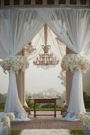 Ok i know this looks crazy elaborate.  But i know the curtains are easy, we see them all the time on beach wedding arches...we could put bougainvillea flowers tied around them the same way these are.  It would save us money on flowers as long as the curtains were full like these ones....as for the chandelier....well that's a bit much anyway!
