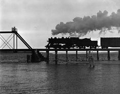 Lake Charlevoix is seen under the south railroad trestle as a train is just about to cross the bridge. Charlevoix Michigan, Lake Huron, Historical Images, Northern Michigan, Marina Bay Sands, Trains, Past, Transportation, Bridge