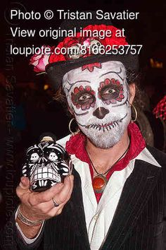 Man with sugar skull makeup, holding sugar skull bottle. Photo taken at the Dia de los Muertos procession in the Mission (San Francisco) on Nov 2, 2012. For more info on this event, please check out my Dia de los Muertos series.  day of the dead, face painting, Facepaint, Halloween, hat, necklace, night, people, red.