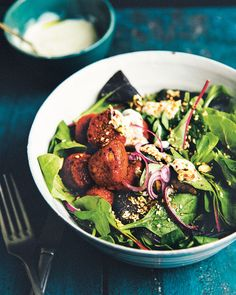 Nina Olsson's falafel have more to offer than meets the eye. They're boosted with heat from harissa and make a great partner for the salad of fresh greens and mint.