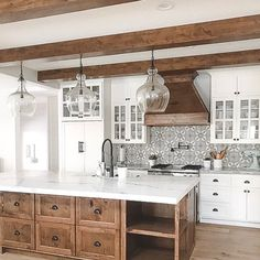 White with Stained Wood and Large Clear Pendant Lights over the Island  WIth the Wood covered vent hood