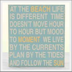 At the Beach Sign. A the beach life is different. Time doesn't move hour to hour but mood to moment. We live by the currents plan by the tides and follow the sun. Hand-painted wood sign with hand-distressed details. Made in the USA.