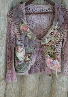 Hay telas y adornos que datan de 1920 a la edad moderna usada para esta pieza. El suave encaje cardi es mohair y angora mezcla, teñido en tonos malva, crema, rubor de la mano... El cuello es adornado con tul Malva polvorienta suave sedoso, pétalos de seda, fibras y abalorios. El frente está adornado con collage de diversos adornos y encajes. Hay brocado francés antiguo de 1920, encajes hechos a mano, ganchillo, encaje metálico Plata patinado antiguo. La chaqueta sujeta con un par de pequeños…