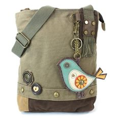 """Patch Crossbody Bag. Stylish Bird key fob included. Casual, fun, and practical.  Fabricated flower & heart shaped wooden button details Top zip closure Antique brass toned hardware Comes with inner lining with zipper and slide pockets Detachable key fob/coin purseMaterials Used: Washed canvas cotton, leather, & textured faux leather Color: Olive  Approx. Measurements: 10"""" x 4"""" x 10.5"""" Strap adjustable: 13""""-26""""  Designed in California. USA Made in China Colors may not be exactly as pi..."""