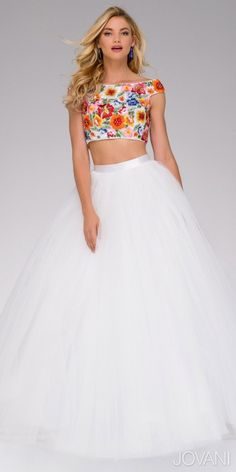 Wow the crowd upon your arrival in this stylish Two Piece Floral Print Tulle Ball Gown by Jovani. This stunning style includes an off the shoulder neckline with cap sleeves and a concealed center back zipper. The bodice is striking and playful as it is embroidered with a multi color floral print and a few beads. The tulle skirt of this style creates an A-line silhouette ball gown appearance with a satin waistband. #edressme