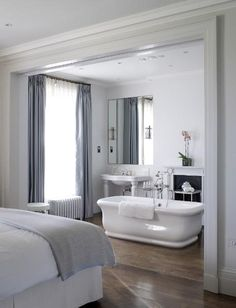 Richard Powers Photography  blue & gray elegant open master bathroom design with freestanding soaking tub, white pedestal sink, fireplace and blue silk drapes.