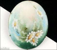 Description: Antique oval hand painted floral motif porcelain brooch, decorated with daisies and greenery, brass setting. Designer/Makers Marks, Hallmarks, Tags: Unsigned. Age: Circa 1920's-1940's. Di