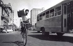 Hombre en bicicleta, camión ruta Lindavista, al fondo la torre Latinoamericana en construcción, México y su vida cotidiana. Años 50's