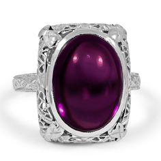 lovely Edwardian ring in white gold. A striking oval amethyst cabochon is complemented by delicate latticework in the gallery and sculpted d...