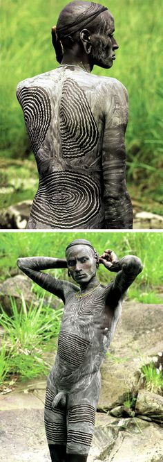 "Africa | ""Surma men create their principal body decoration by smearing the skin with a mixture of chalk and water and drawing intricate designs with their wet fingertips to expose the dark skin underneath"" Ethiopia. 