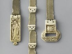 Belt with ivory buckle, pendant and stops (ceinture): Paris, Musée de Cluny-Musée national du Moyen Âge Cl. 11982 Ivory;wool Height: 168mm (total); 56mm (buckle); 80mm (pendant) Width: 20mm (strap); 50mm (buckle); 25mm (pendant) Buckle: Holy Face of Christ (Sancta Facies); foliated decoration. Pendant: saint Dominic with a cross, dog holding a flaming torch. Saint Catherine of Siena with the devil at her feet, a cross and a crown of thorns. Crosshatched background.  Koechlin Number: 1223…