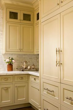 A khaki paneled fridge with khaki paneled freezer drawers is accented with polished nickel handles and positioned beside khaki cabinets topped with a white marble countertop complementing white marble linear backsplash tiles framing khaki upper cabinets finished with a row of glass front display cabinets.