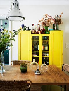 Colourful kitchen: white walls + wood + plants + yellow cabinet
