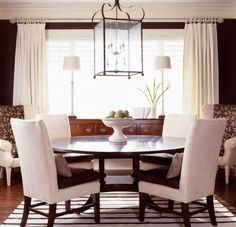 Simple symmetry  This dining room sports an assortment of subdued patterns and textures in a striped cotton rug, leather seat cushions, houndstooth pillows, diamond-embroidered drapes and floral upholstery. Simple ivory pottery pieces provide the only accents needed.