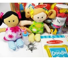 Basic Play Therapy Starter Kit Zoom In- ethnically diverse dolls, baby bottles, sheriff badge, Melissa and Doug paper, and Kimochis close up