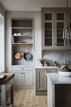 A serene farmhouse kitchen design with warm putty gray painted kitchen cabinets, beadboard, and marble backsplash in a gorgeous classic kitchen. Kitchen Corner, New Kitchen, Kitchen Decor, Kitchen Ideas, Kitchen Paint, Warm Kitchen, 1970s Kitchen, Awesome Kitchen, Hanging Pots Kitchen