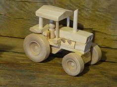 Handmade original design wood toy farm tractor. 6 1/2 inches long and 3 3/4 inches wide, wheels all turn and comes with 1 little wood person for seat. Made from pine, spruce, maple (wheels), and glued together with non-toxic child safe glue. The tractor has no oils, stains, or finishes