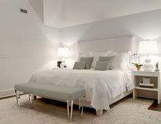 White and gray bedroom features a white bed lined with gray pillows as well as a matching gray lucite bench placed at the foot of the bed flanked by white open nightstands and white double gourd lamps.